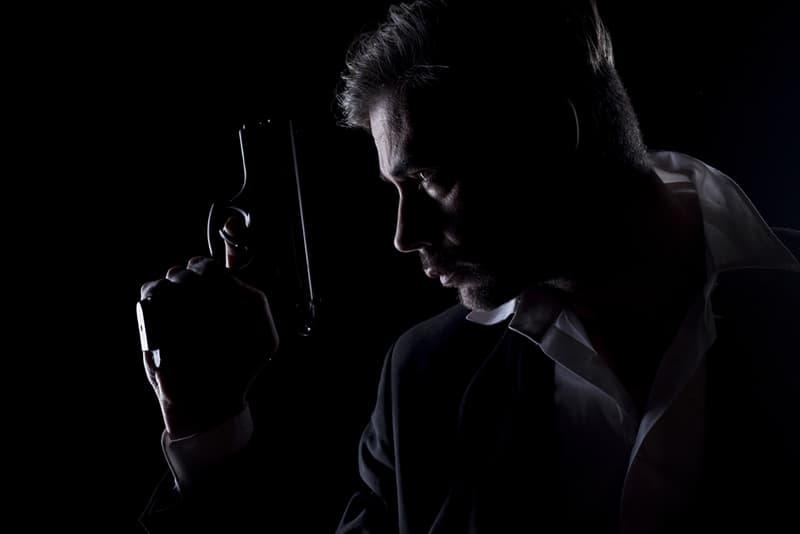 Männer Silhouette im Dunkeln mit einer Waffe in der Hand