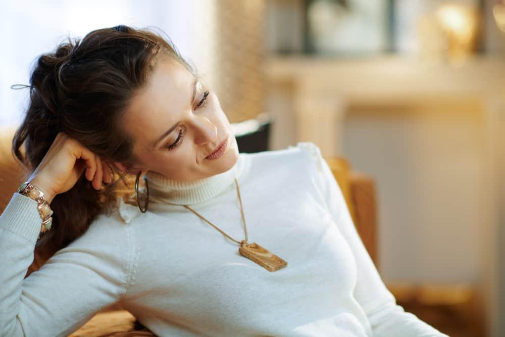 Im Haus in einem weißen Pullover sitzt eine traurige Frau und denkt nach