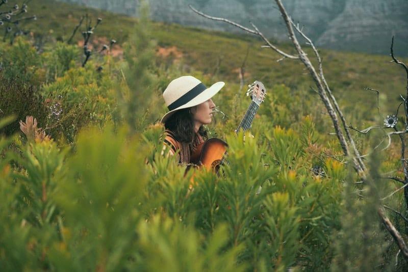 Im hohen Gras spielt eine Frau Gitarre
