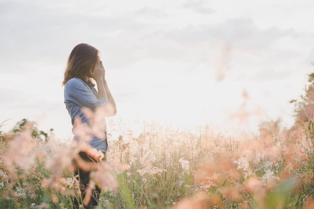 In einem Blumenfeld bei Sonnenuntergang steht eine traurige Frau