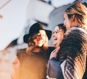 Drei Frauen lachen und reden draußen