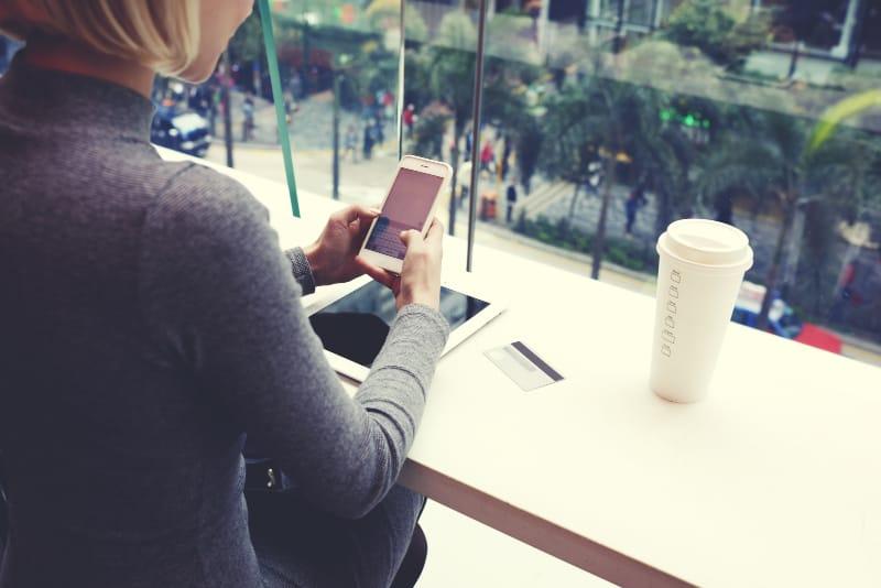 Mädchen sitzt in einer Cafeteria, Knopf am Handy