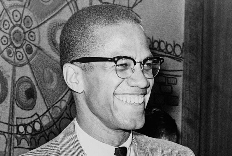 Malcolm X lächelnd zur Seite schauen