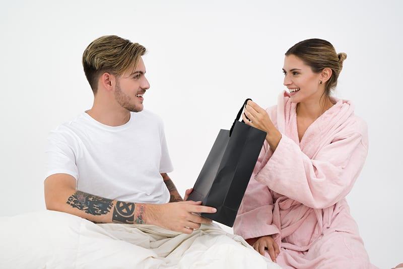 Mann, der seiner Freundin ein Geschenk in einer schwarzen Papiertüte gibt, während er zusammen auf dem Bett sitzt