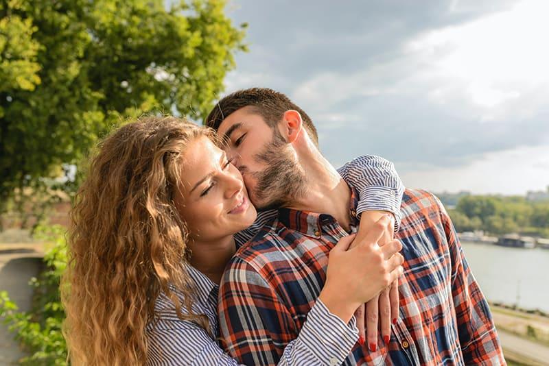 Mann küsst eine Frau auf eine Wange, während sie ihn von hinten umarmt