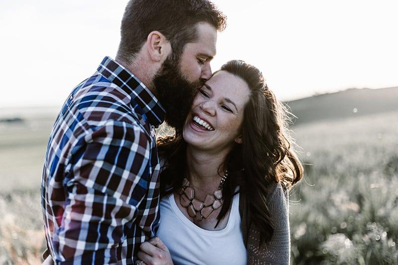 Mann küsst eine lächelnde Frau auf eine Wange, während er sich umarmt