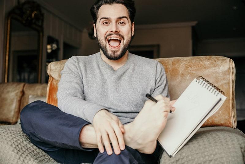 Mann schreibt einen Text in das Notizbuch mit den Zehen des Fußes, während er auf der Couch sitzt