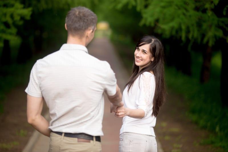 Mann und Frau in der Natur Händchen haltend