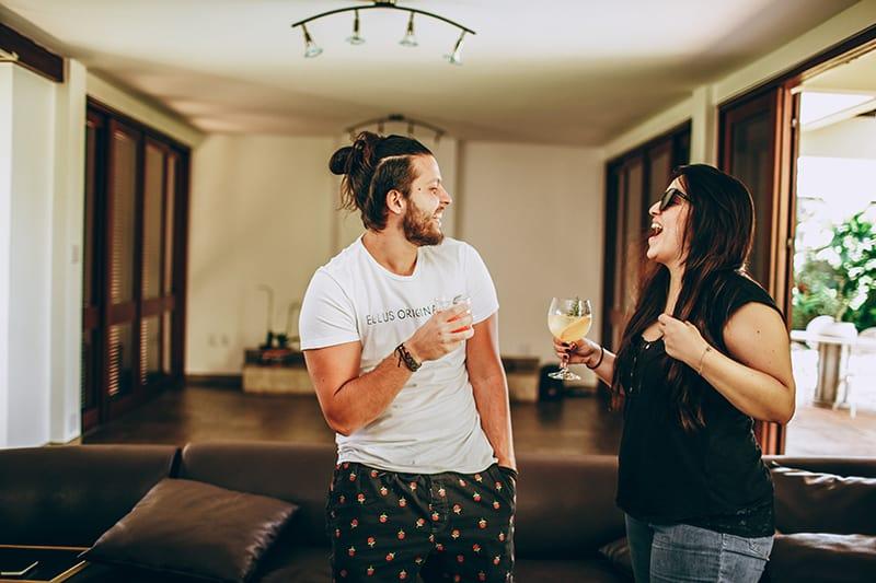 Mann und Frau lachen, während sie Getränke halten und sich im Wohnzimmer ansehen