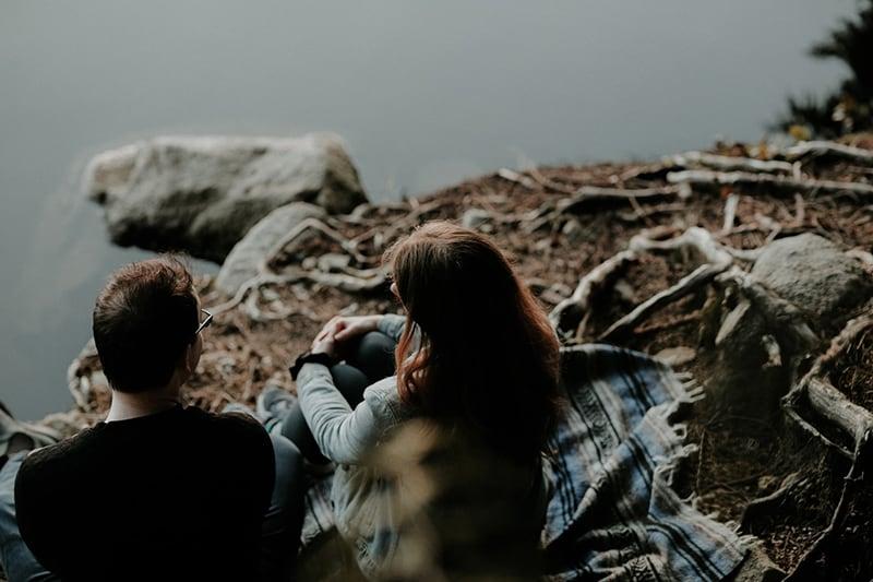 Mann und eine Frau sprechen, während sie in der Nähe des Sees sitzen