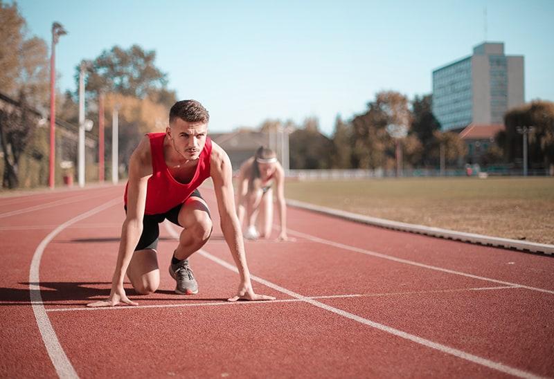 Mann und Frau stehen an der Startlinie des Stadions und bereiten sich auf das Laufen vor