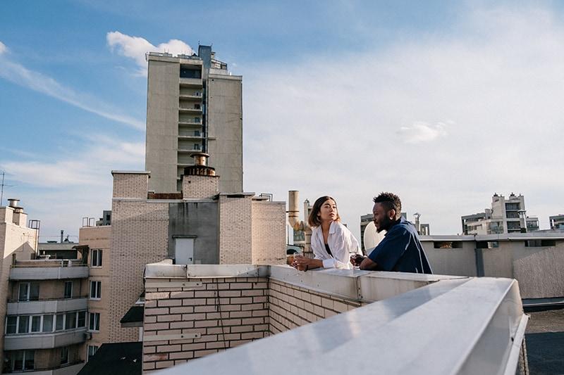 Mann und Frau unterhalten sich auf dem Dach und trinken Wein