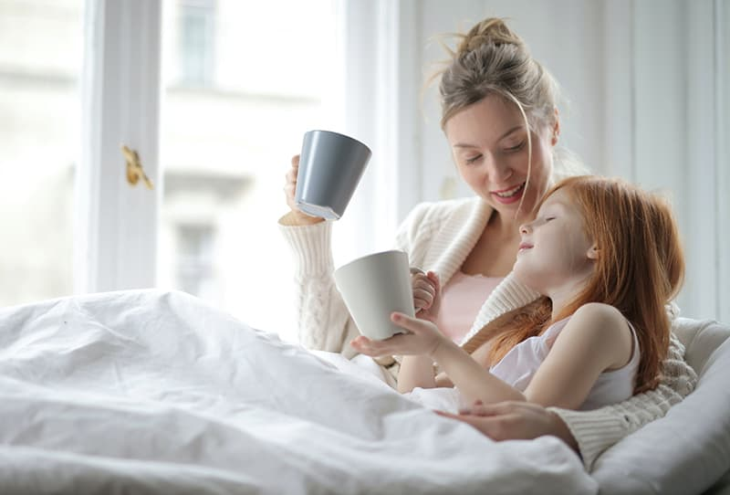 Mutter und Tochter liegen in einem Bett und halten Keramikbecher