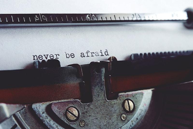 Schreibmaschine mit weißem Papier und Text in Englisch