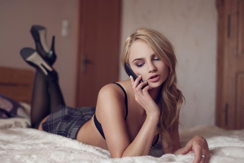 Sexy blonde Frau, die am Telefon spricht, während sie auf dem Bett liegt