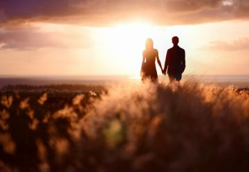 Ein Paar geht der Sonne entgegen