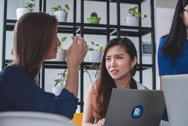 eine Frau, die überrascht aussieht, während sie ihren Kollegen ansieht