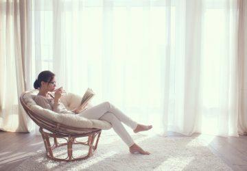 eine Frau, die im Haus auf einem modernen Stuhl sitzt und Tee trinkt