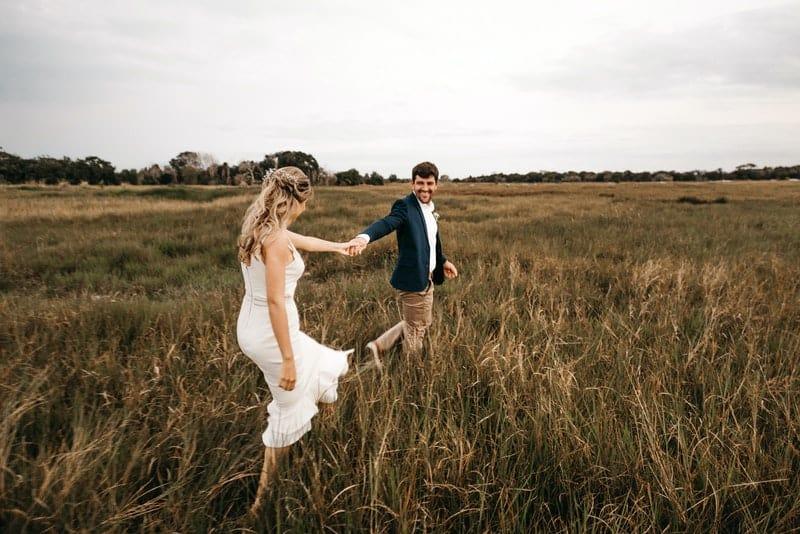 Braut und Bräutigam gehen lächelnd über das Feld
