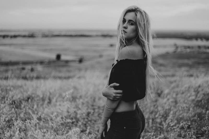 eine Frau mit langen blonden Haaren steht