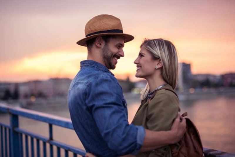 ein Paar, das auf einer Brücke steht und einander in die Augen schaut
