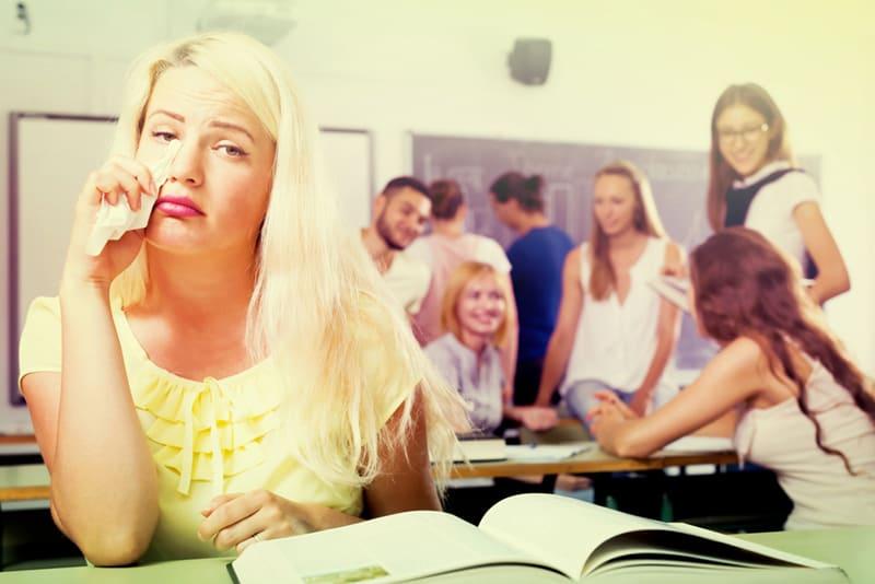Weinende Studentin, die im Klassenzimmer sitzt und Tränen abwischt