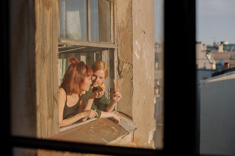 Zwei Frauen lehnen sich an das Fenster eines alten Gebäudes und essen Pizza