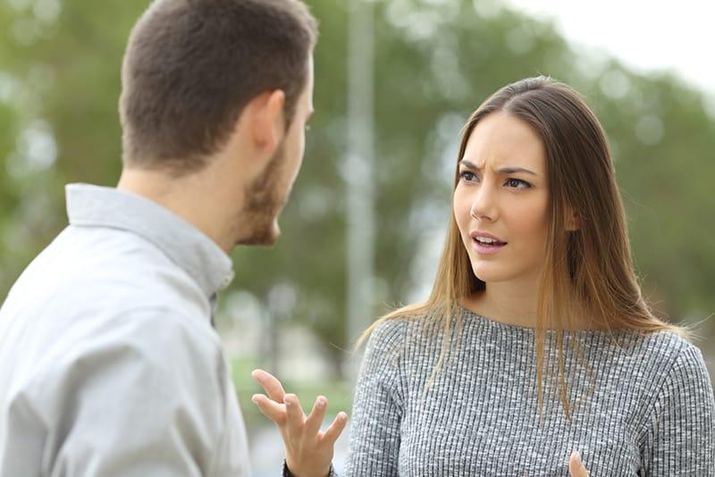 beleidigte Frau, die mit einem Mann spricht, während sie zusammen im Park stehen