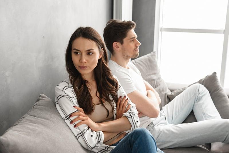 die eifersüchtige Frau, die neben ihrem verärgerten Freund auf der Couch sitzt