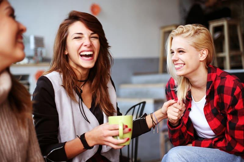 Drei Frauen lachen zusammen im Cafe