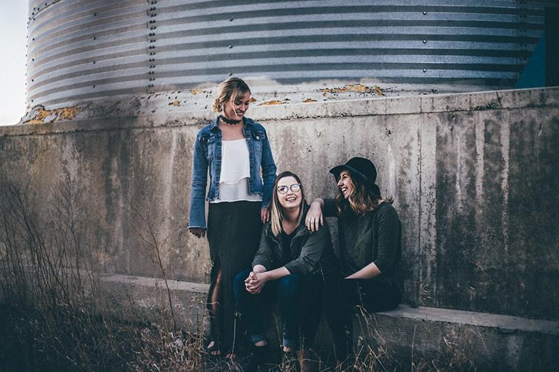 Drei Freundinnen hängen in der Nähe der Betonmauer