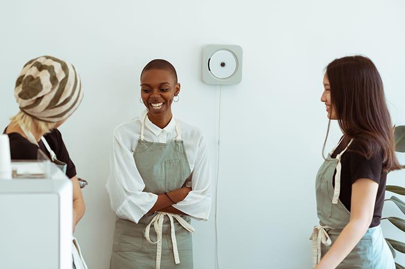 Drei Kolleginnen lachen, während sie sich in einer Pause unterhalten