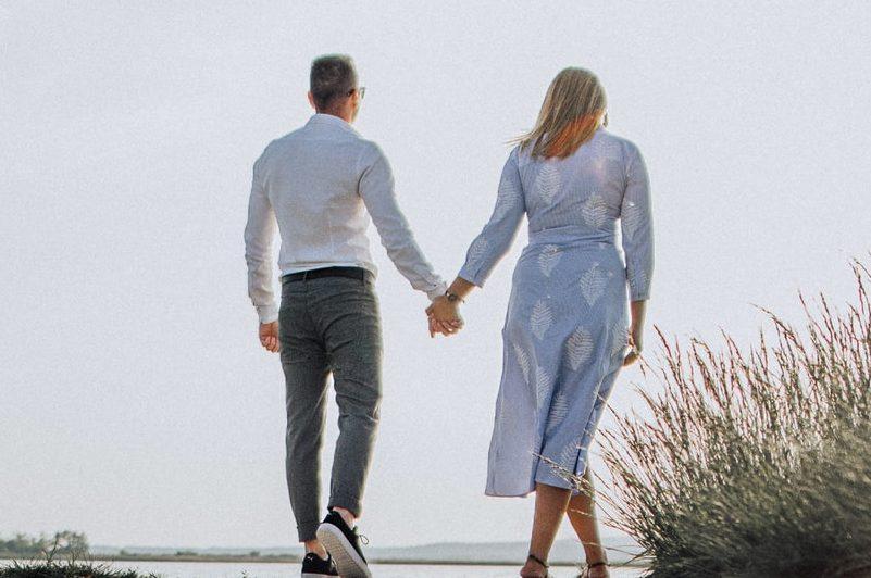 ein Mann Händchen haltend mit einer Frau am Strand