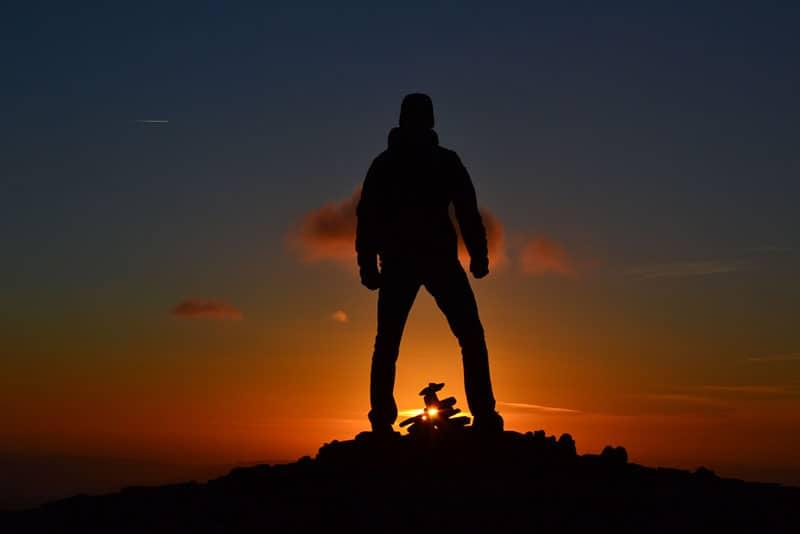 ein Mann, der auf einem Hügel bei Sonnenuntergang steht