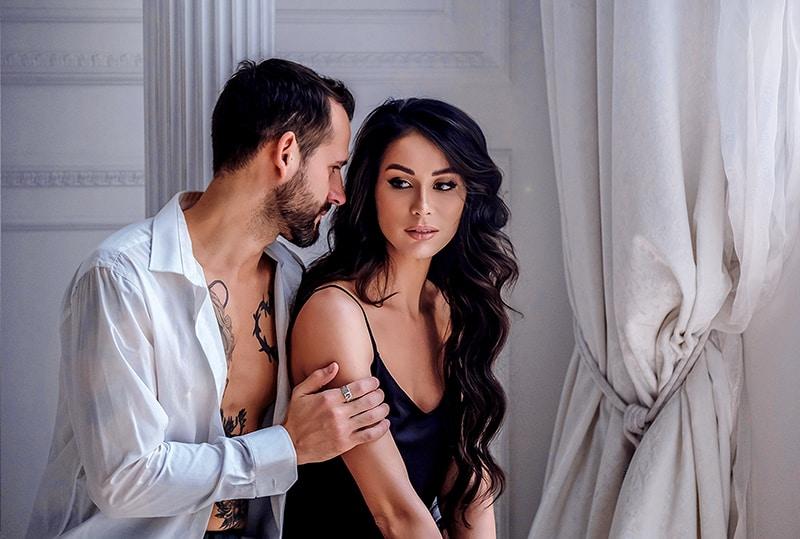 Ein Mann berührt die Hand einer Frau, während er im Schlafzimmer neben ihr steht