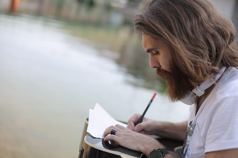 Ein Mann schreibt ein Gedicht auf Papier, während er in der Nähe des Gewässers sitzt