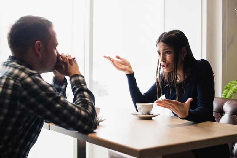 Ein Mann hört einer Frau zu, die im Café ein Drama spielt