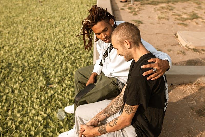 Ein Mann tröstet seinen Freund, während er im Park sitzt