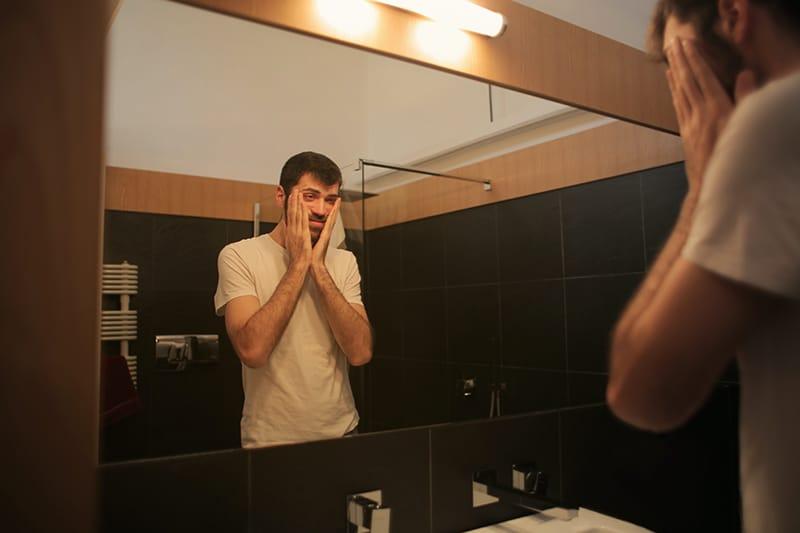 Ein Mann, der sich selbst in den Spiegel schaut und dabei das Gesicht mit den Händen berührt