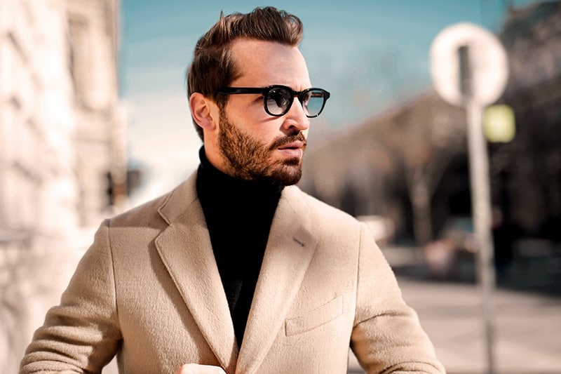 Ein Mann im braunen Mantel sieht verwirrt aus, als er auf der Straße geht