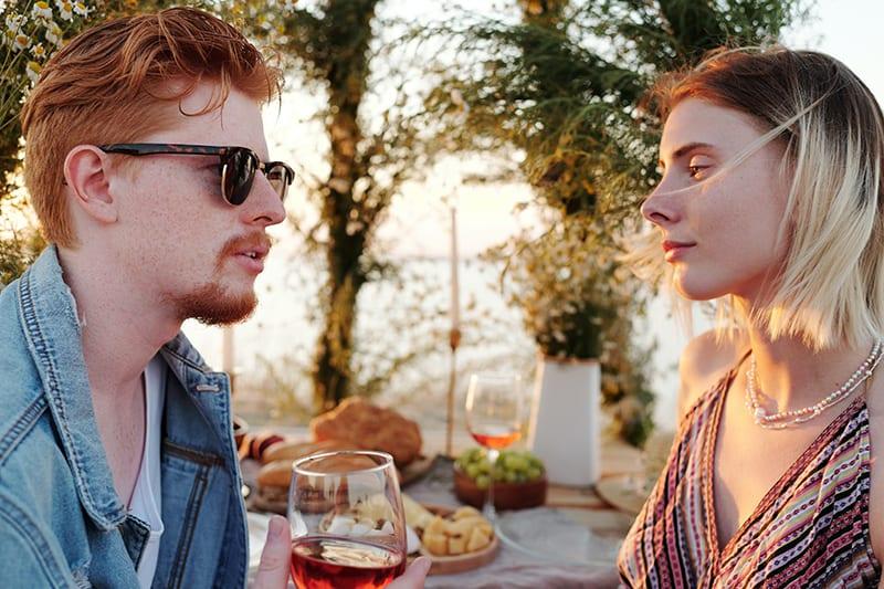 Ein Mann hält ein Glas Wein und spricht mit einer Frau während eines Mittagessens im Freien