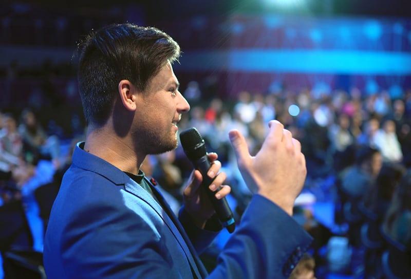 ein Mann, der ein Mikrofon hält und eine Rede hält