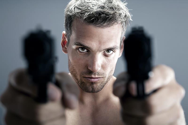 ein hemdloser Mann mit zwei Waffen
