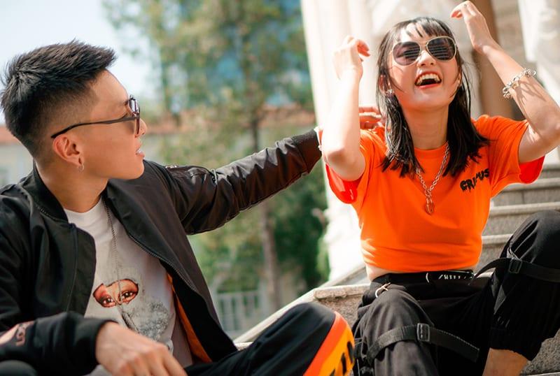 Ein Mann und eine lachende Frau sitzen dicht nebeneinander auf der Treppe