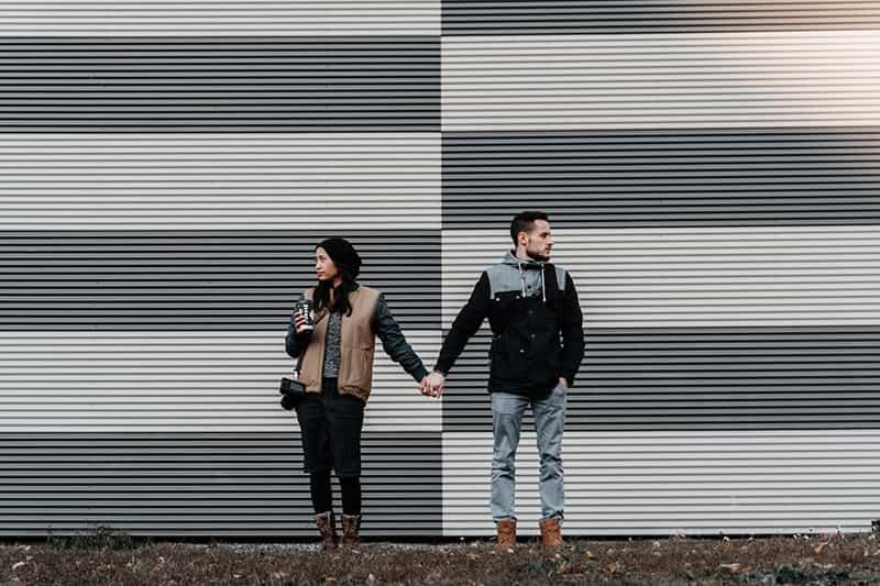 ein Paar, das sich an der Hand hält und in verschiedene Richtungen schaut, während es vor der Garage steht