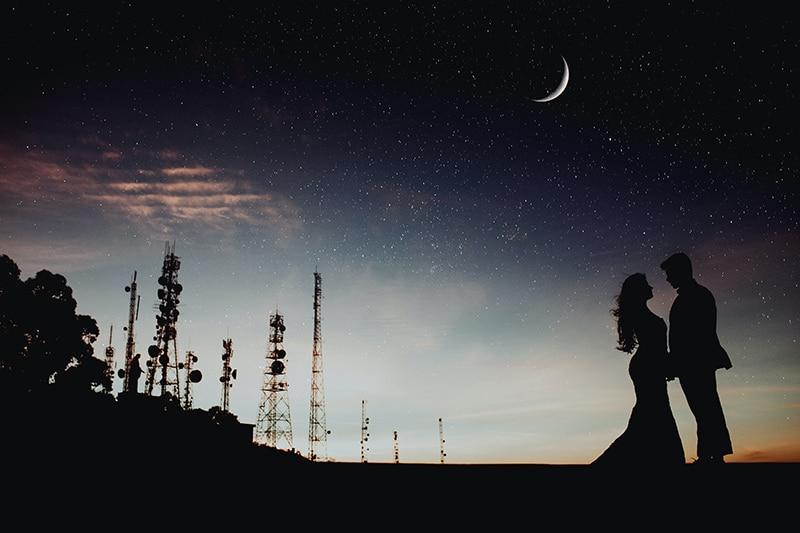 ein Paar, das in der Nacht unter dem Mond und den Sternen steht