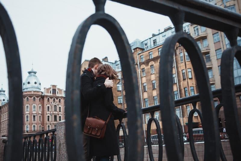 ein Paar in einer Umarmung, das auf einer Brücke steht