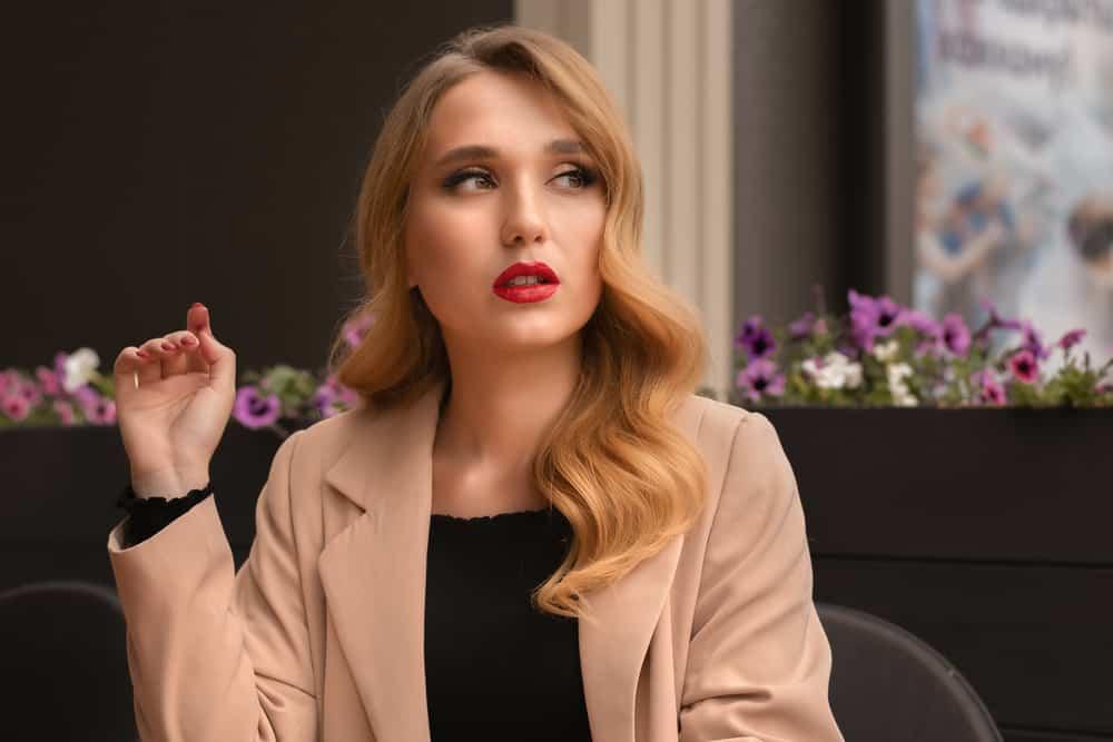 ein Porträt einer schönen Blondine, die sitzt und denkt