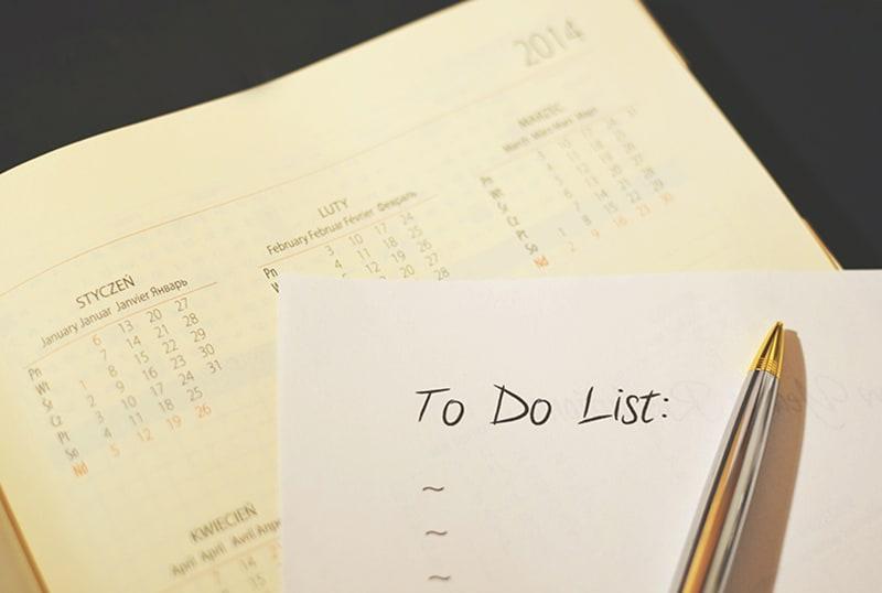 ein Whitepaper mit Aufgabenliste und Stift darauf auf dem Kalender
