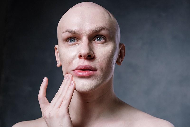 ein kahlköpfiger Mann mit gruselig aussehendem Gesicht mit der Hand